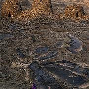 Oman, Al-Ayn. January/30/2008...Women making their way towards Hafit tombs at Al-Ayn as the sun sets.