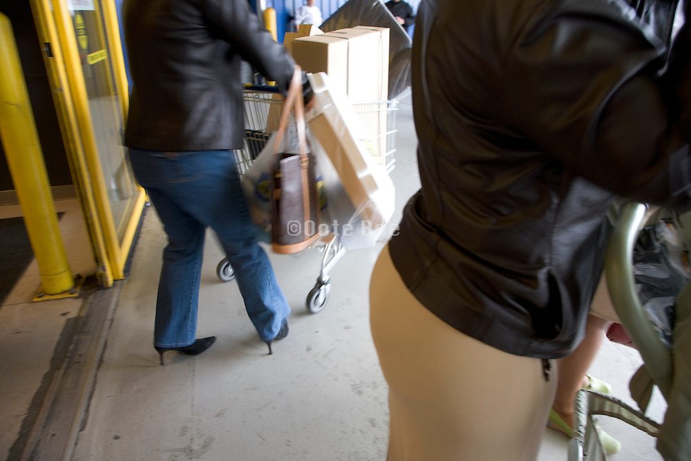 woman coming out of a department store with loaded shopping carts