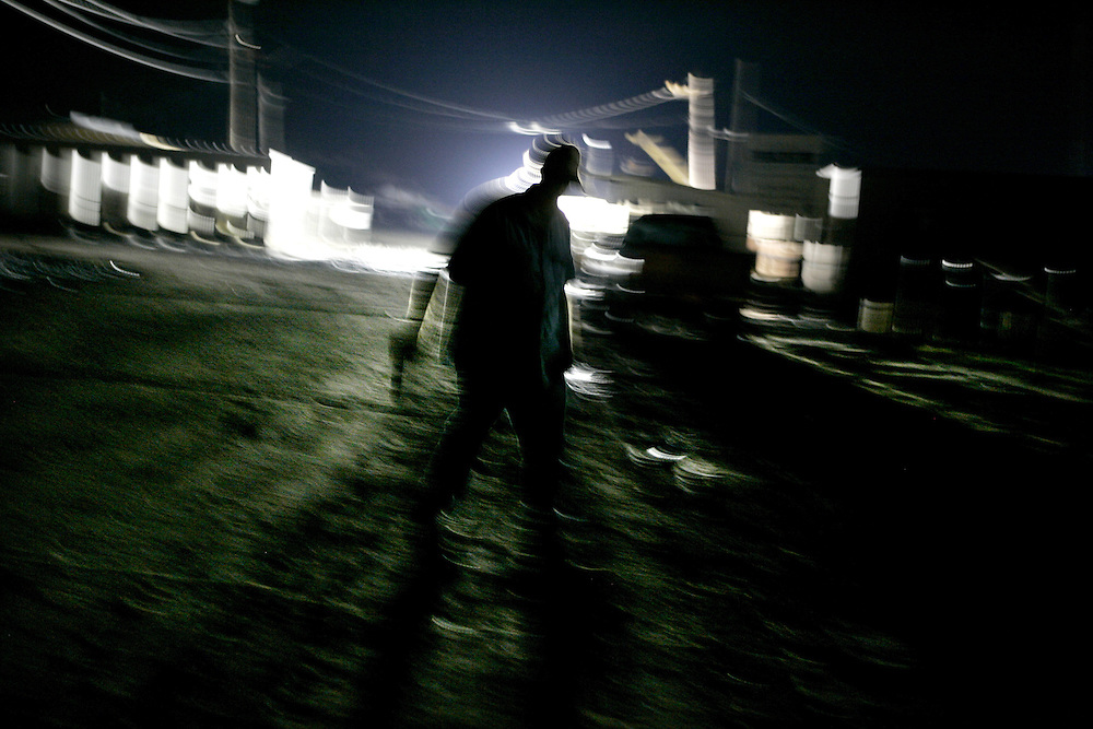 Danny Prewitt walks around the perimeter of the Signal International shipyard in Orange, Texas, while standing guard overnight with 5 coworkers Wednesday September 17, 2008.  Thick mud covered the area, washed in by Hurricane Ike.  At the time there was no word yet on when operations would be back to normal at the shipyard.
