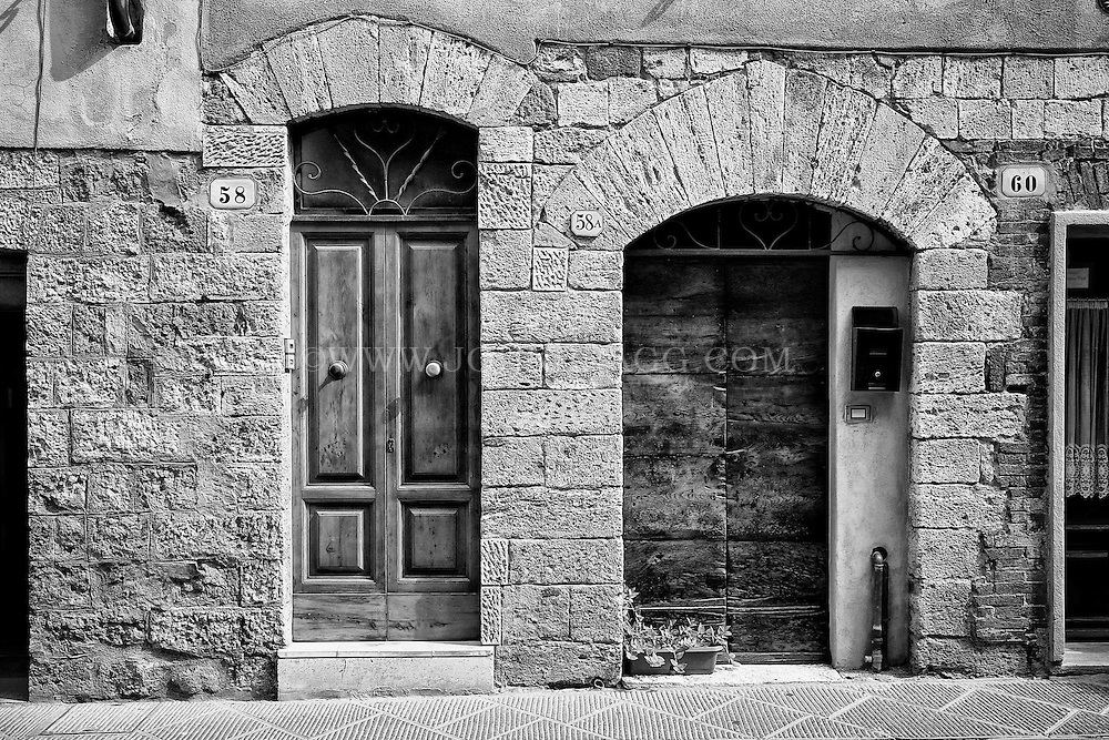 Black and white image of neighboring doorways along the street in San Quirico d'Orcia, Italy.
