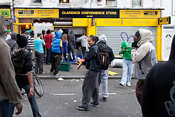 © Licensed to London News Pictures . FILE PICTURE DATED 08/08/2011. Hackney , UK . A young woman laughs as looters break in to the Clarence Convenience Store on Clarence Road . People riot and loot on the Pembury Estate in Hackney . Following a night of riots and looting in Tottenham , rioting and looting spreads to other areas . Photo credit : Joel Goodman/LNP
