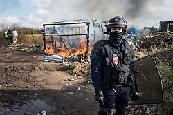 Licensed to London News Pictures. Calais, France. 03/03/16.  French riot police keep volunteers and refugees away from a burning shelter. French authorities are clearing the southern half of the Calais 'Jungle' camp, which charities estimate to contain 3,500 people.. Photo credit : Rob Pinney/LNP