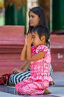 YANGON, MYANMAR - DECEMBER 16, 2016 : woman and her child praying at Shwedagon Pagoda Yangon (Rangoon) in Myanmar (Burma)