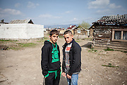 Two teenagers posing for a portrait at the Roma settlement in Ostrovany. In 2010, the town of Ostrovany received international media attention when the town council built a wall deviding private gardens/property and the neighbouring Roma settlement. Several media outlets compared the look of Ostrovany's imposing 150-metre long wall with the Berlin Wall.