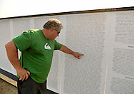 East Meadow, New York, U.S. 11th September 2013. MIKE BERNSTEIN, of East Meadow, points to the name of his friend, NYC firefighter Daniel Suhr, who, Bernstein explained, died when someone who jumped from window of Twin Tower landed on him as Suhr was rushing into the tower. The Global War on Terror Wall of Remembrance, a traveling memorial on display in New York for the first time, was at Eisenhower Park on the 12th Anniversary of the terrorist attacks of 9/11. The unique 94 feet long by 6 feet high wall has, on one side, almost 11,000 names of those lost on September 11th 2001, along with heroes and veterans who lost their lives defending freedom of Americans over past 30 years.