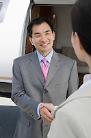 Mid-adult Asian businessman shaking hands with mid-adult businesswoman in front of private plane.