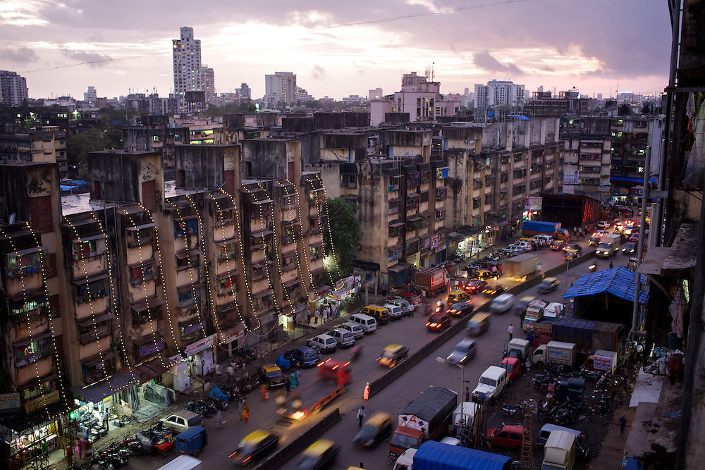 Evening traffic passes through new housing in Dharavi slum, behind which can be seen the high-rise accomodation of wealthier neighbourhoods. Dharavi is home to more than 1m people. Traffic congestion and the safety of pedestrians is an issue in much of Mumbai. ..The BMC (Brihanmumbai Municipal Corporation) uses the UNDP-devised Human Development Index (HDI) as a measure by which to allocate resources. ..Using parameters like population, literacy rate and infant mortality, and ranking wards in the order of performance, the BMC apportions funds to areas with lower education and higher mortality rates. The BMC also encourages the participation of Mumbai's citizens in the monitoring of education and health projects...Photo: Tom Pietrasik.Mumbai, India.September 6th 2010.