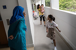 March 15, 2014 - Singapore. Tutik works full time (7 days a week) looking after Izzati (7), in the morning she will take Izzati to the school bus which picks her up at her grandparents house. © Nicolas Axelrod / Ruom
