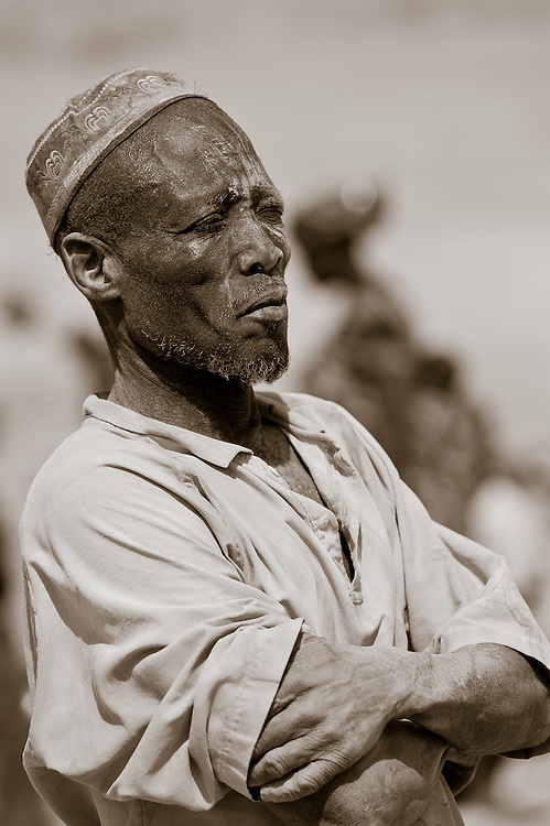 Portrait of a stern watchful man observing activities at an artisanal gold mining site in northern Burkina Faso