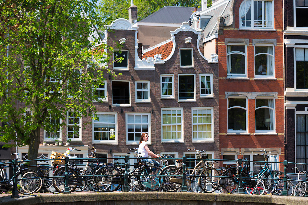 Canalside cyclists house and bridge at Herengracht / Singel in Jordaan District of Amsterdam, Holland