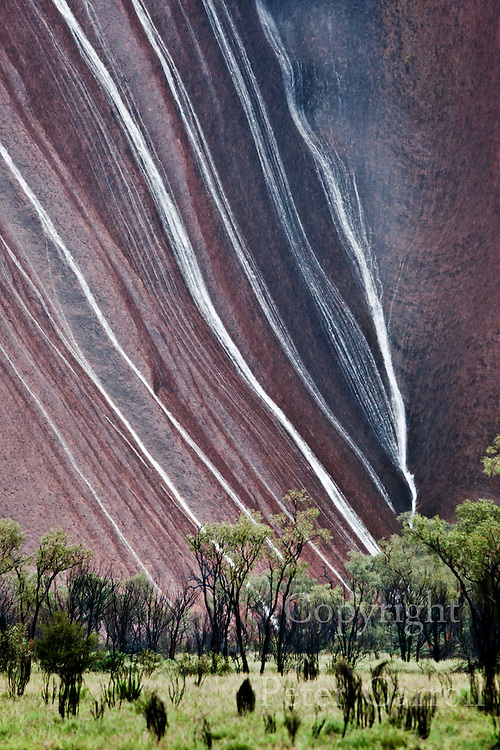 14 Oct 2010 Water pours down the red surface of Uluru after torrential rain