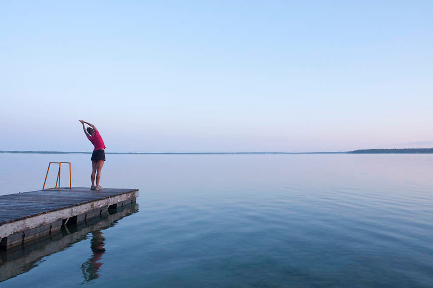 Runner stretching by Clear Lake,<br /> Manitoba in the early morning. The young 20 year old athlete does yoga before her run.