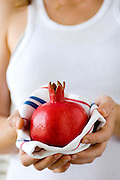 Woman offering a perfect red ripe pomegranate