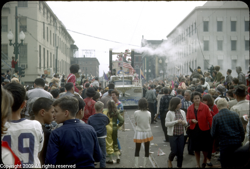 Revelers participate in the 1966 Mardi Gras parade in New Orleans, Louisiana. A street is filled with parade goers.