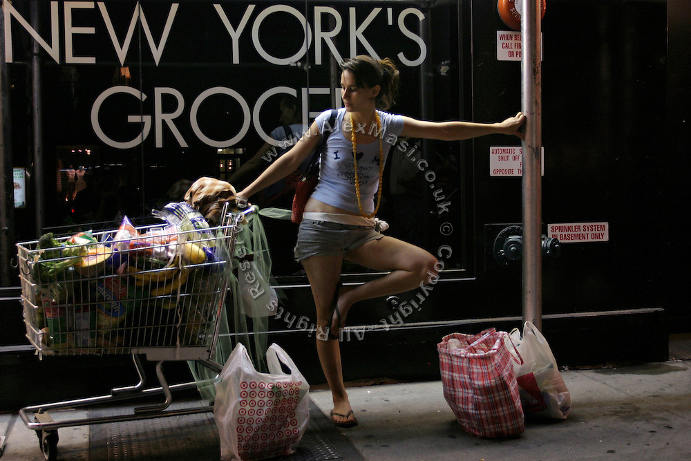 Stephanie, 21, member of the Freegan community in New York, standing by the food recovered from dump sites along 3rd Avenue in Manhattan, New York, NY., on Wednesday, July 5, 2006. Freegans are a community of people who aims at recovering wasted food, books, clothing, office supplies and other items from the refuse of retail stores, frequently discarded in brand new condition. They recover goods not for profit, but to serve their own immediate needs and to share freely with others. According to a study by a USDA-commissioned study by Dr. Timothy Jones at the University of Arizona, half of all food in the United States is wasted at a cost of $100 billion dollars every year. Yet 4.4 million people in the United States alone are classified by the USDA as hungry. Global estimates place the annual rate of starvation deaths at well over 8 million. The massive waste generated in the process fills landfills and consumes land as new landfills are built. This waste stream also pollutes the environment, damages public health as landfills chemicals leak into the ground, and incinerators spew heavy metals back into the atmosphere. Freegans practice strategies for everyday living based on sharing resources, minimizing the detrimental impact of our consumption, and reducing and recovering waste and independence from the profit-driven economy. They are dismayed by the social and ecological costs of an economic model where only profit is valued, at the expense of the environment. In a society that worships competition and self-interest, Freegans advocate living ethical, free, and happy lives centred around community and the notion that a healthy society must function on interdependence. Freegans also believe that people have a right and responsibility to take back control of their time.