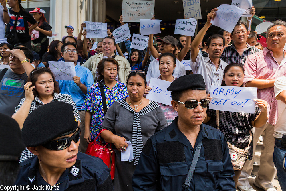 25 MAY 2014 - BANGKOK, THAILAND: Thai police stand in front of protestors opposed to the military junta at a demonstration in Bangkok. Public opposition to the military coup in Thailand grew Sunday with thousands of protestors gathering at locations throughout Bangkok to call for a return of civilian rule and end to the military junta.      PHOTO BY JACK KURTZ