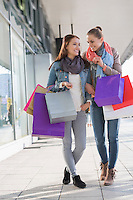 Happy female friends communicating while carrying shopping bags on sidewalk