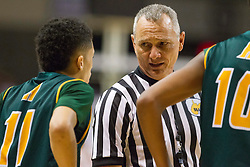 A referee talks with Huntington guard Tavian Dunn-Martin (11) after an altercation during a semi-final game at the Charleston Civic Center.