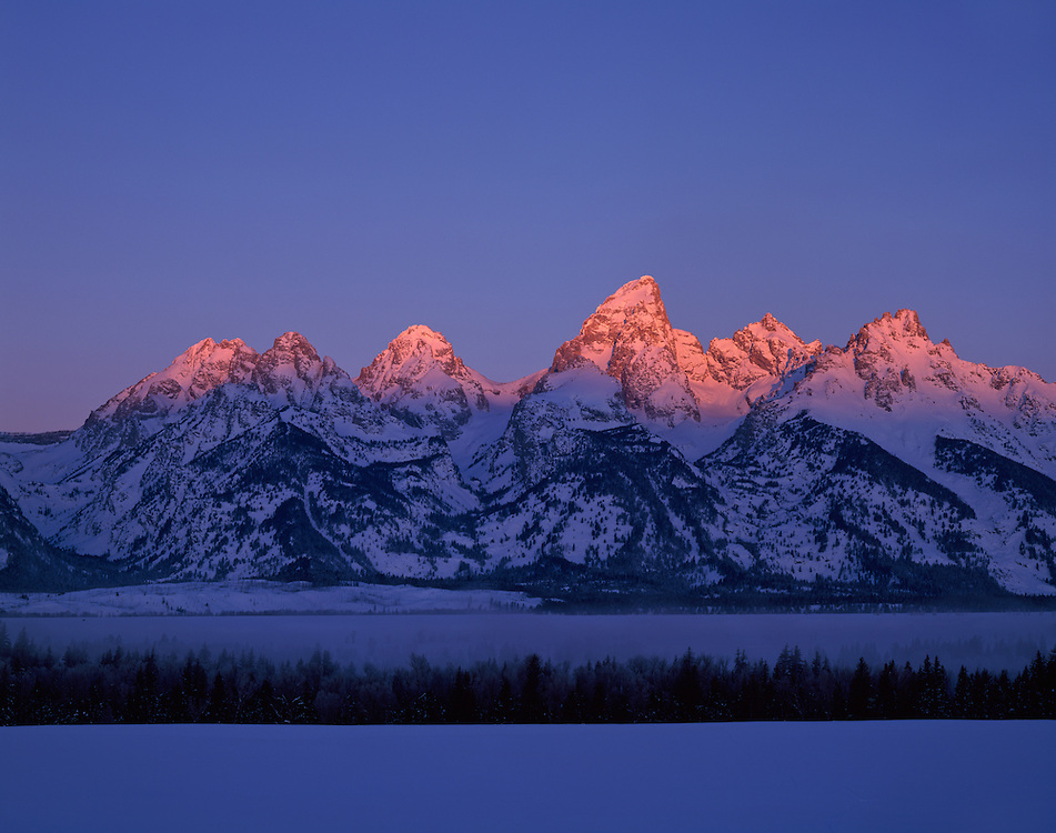 The Teton Range at sunrise is a mountain range of the Rocky Mountains in North America. A north-south range, it is on the Wyoming side of the state's border with Idaho, just south of Yellowstone National Park. Most of the range is in Grand Teton National Park.<br /> <br /> Early French Voyageurs used the name &quot;les Trois T&eacute;tons&quot; (the three breasts).[1] It is likely that the Shoshone people once called the whole range Teewinot, meaning &quot;many pinnacles&quot;.[2]<br /> <br /> The principal summits of the central massif, sometimes referred to as the Cathedral Group, are Grand Teton (13,770 feet (4,200 m)), Mount Owen (12,928 feet (3,940 m)), Teewinot (12,325 feet (3,757 m)), Middle Teton (12,804 feet (3,903 m)) and South Teton (12,514 feet (3,814 m)). Other peaks in the range include Mount Moran (12,605 feet (3,842 m)), Mount Wister (11,490 feet (3,500 m)), Buck Mountain (11,938 feet (3,639 m)) and Static Peak (11,303 feet (3,445 m)).
