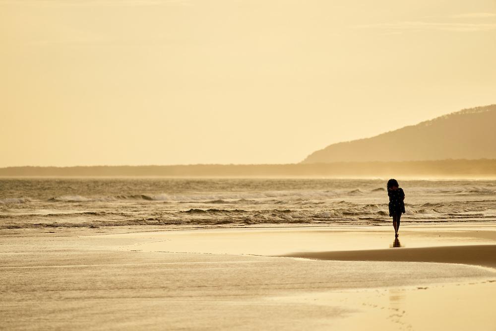 Woman walking on 7 Mile Beach, Gerroa, South Coast, NSW, Australia at sunset.