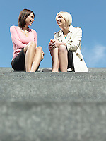 Two women sitting and talking on stairs outdoors low angle view