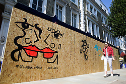 © Licensed to London News Pictures. 22/08/2019. London, UK. A woman walks past a residential property which has been boarded ahead of the 2019 Notting Hill Carnival in West London, which takes place this bank holiday weekend. Up to 1 million people are expected to attend the biggest street party in Europe. Photo credit: Dinendra Haria/LNP