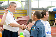 Proud athlete shakes hands with policeman at award ceremony. Special Olympics U of M Bierman Field. Minneapolis Minnesota USA
