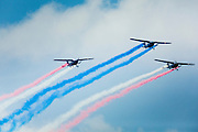 29 SEPTEMBER 2014 - NAKHON NAYOK, NAKHON NAYOK, THAILAND: Thai army airplanes generating exhaust in the colors of the Thai flag fly over the retirement ceremony for more than 200 Thai generals including Gen. Prayuth Chan-ocha, who led the 22 May coup against the civilian government earlier this year. Prayuth has been chief of the Thai army since 2010. After his retirement, Gen. Prayuth will retain his posts as head of the junta's National Council for Peace and Order (NCPO) and Prime Minister of Thailand. Under Thai law, military officers must retire at 60 years of age. The 200 generals who retired with Prayuth were also his classmates at the Chulalomklao Royal Military Academy in Nakhon Nayok.    PHOTO BY JACK KURTZ
