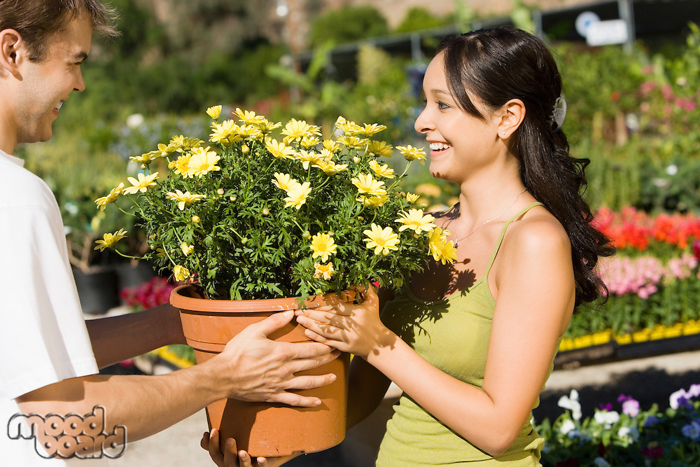 Smiling Couple Shopping for Large Potted Plant