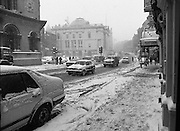 Dublin Snow Scenes.  (R48)..1897..14.01.1987..01.14.1987..14th January 1987..Following unprecedented overnight snow Dublin City almost came to a standstill.There was severe traffic disruption and many events scheduled for city centre venues were cancelled...Image shows a view down Dame Street toward City Hall as the snow continued to fall.Traffic is shown crawing towards the city centre,even the footpaths were treacherous.