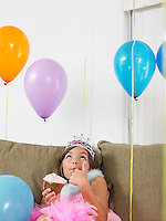 Young girl (7-9) sitting on sofa eating cupcake looking up at balloons