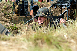 Reenactors portraying a soldier from the Panzer Grenadier Division Großdeutschland take part in a small scale skirmish during a living history display at Ackworth Steam Rally