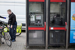 © Licensed to London News Pictures . 06/04/2017 . Manchester , UK . A paramedic tends to a man , believed to have consumed spice , in Piccadilly Gardens , as another man consumes a rolled cigarette believed to contain spice , in an adjacent telephone box . An epidemic of abuse of the drug spice by some of Manchester's homeless population , in plain sight , is causing users to experience psychosis and a zombie-like state and is daily being witnessed in the Piccadilly Gardens area of Manchester , drawing large resource from paramedic services in the city centre . Photo credit : Joel Goodman/LNP
