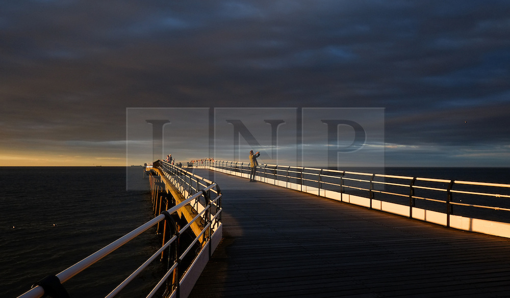 © Licensed to London News Pictures.06/08/15<br /> Saltburn, UK. <br /> <br /> A man takes a picture at sunset at Saltburn by the Sea in Cleveland. <br /> <br /> Photo credit : Ian Forsyth/LNP