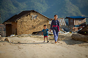Children walk through a village currently being reconstructed after being almost completely destroyed during the 2015 earthquake