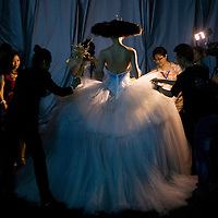 BEIJING, MAY -7, 2012 : China's top fashion designer Guo Pei ( L) takes a last look at one of her creations before  she sends a model  on the catwalk ...Guo Pei , 45, is China's answer to haute couture. When she started out 15 years ago, there was no fashion in China .  Since then though  about everything in China has changed. Many more people are able to afford luxury products, and Chinese women, at least those who can afford it, follow international fashion trends. What makes Guo Pei different is what she puts on a runway. She employs 300 people in a workroom two hours from Beijing. She had to train them, but it?s also true that her creative freedom is tethered to relatively cheap labor. One dress alone, made entirely of golden panels, took 50,000 hours to embroider.