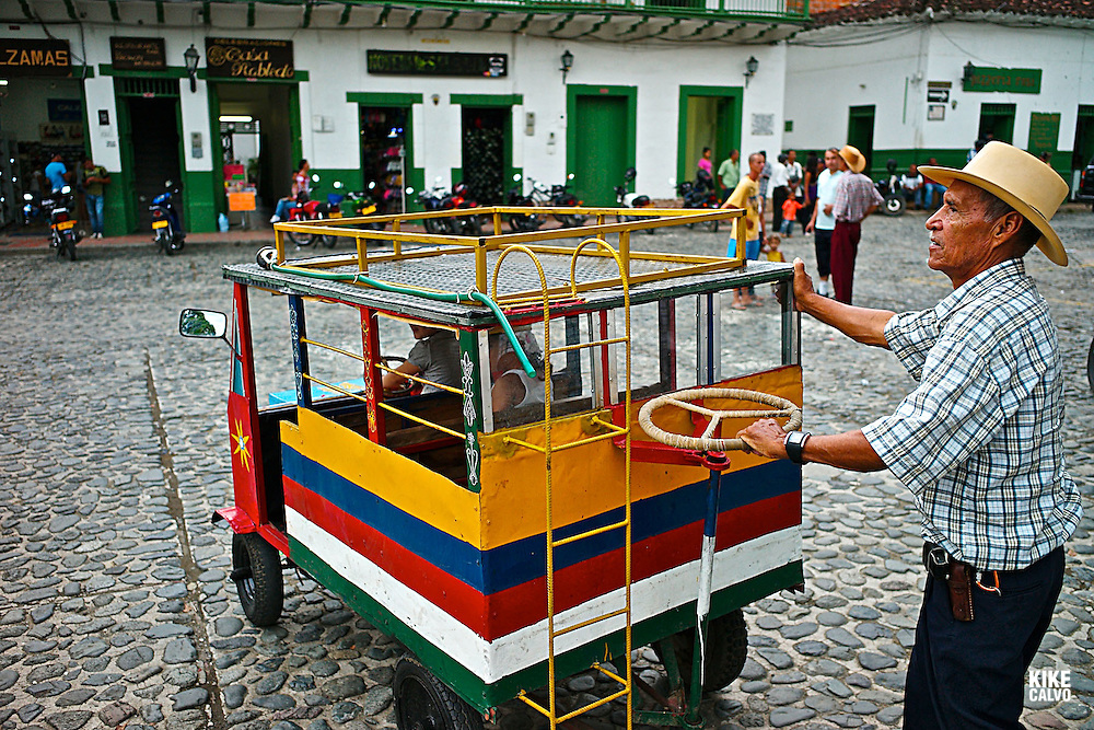 A man in wearing the traditional hat pushes a ¨chiva¨ or bus designed as a children´s game