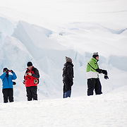 A group of tourists ashore on the ice at Mikkelsen Harbour on Trinity Island, Antarctica.