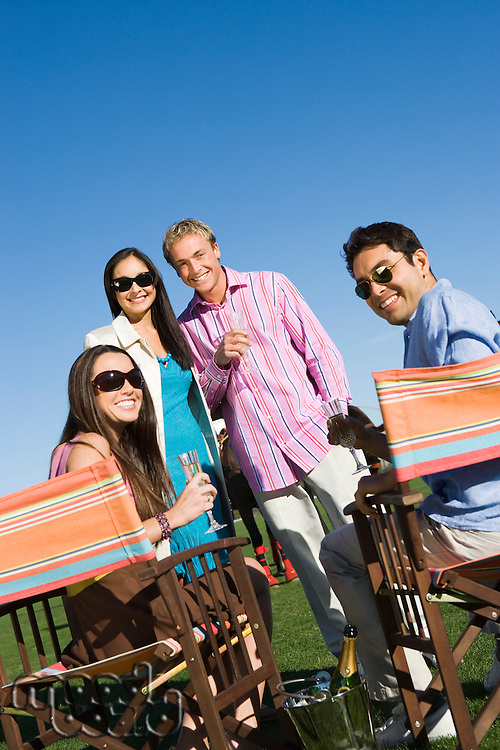 Four friends toasting on polo field, portrait