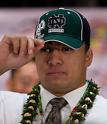 Photo By Eugene Tanner..Manti Te'o adjust his Notre Dame cap after signing his letter of Intent to attend and play football for Notre Dame.
