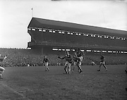 Cork player jumps in an attempt to block the ball from Louth's possession during the All Ireland Senior Gaelic Football Championship Final Louth v Cork at Croke Park on the 22nd September 1957. Louth 1-09 Cork 1-07.