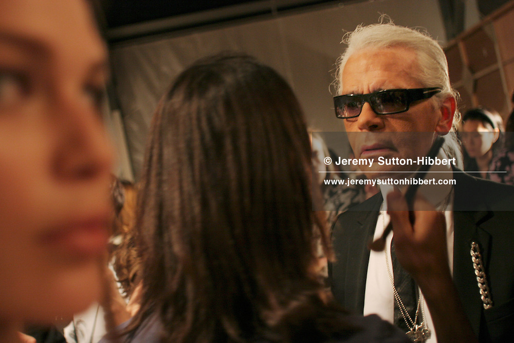 KARL LAGERFELD BACKSTAGE AT CHANEL 'RED CARPET' FASHION SHOW, having his make-up re-touched, in Hibiya Park, Tokyo.