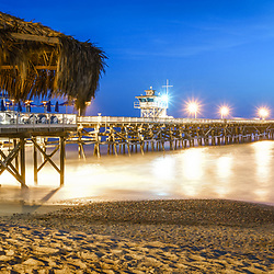 San Clemente California pier and tiki umbrella at night. San Clemente is a popular beach city in Orange County in Southern California in the United States of America. Copyright ⓒ 2017 Paul Velgos with all rights reserved.