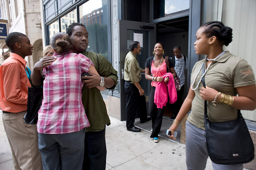 City Charter High School student Richard Walters (left) hugs a friend on Seventh Street as Ashley Gunn leaves the Clark Building during dismissal from school.  At right is student Sidney Lane. Nearly 600 students attend City High.
