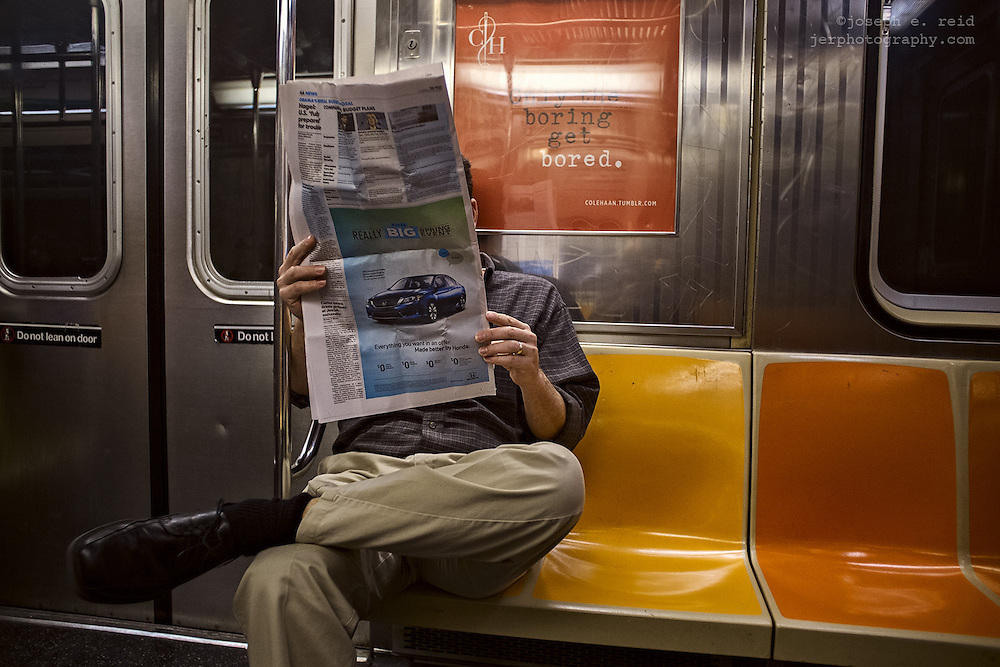 Man on subway reading newspaper