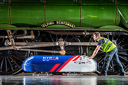 © Licensed to London News Pictures. 26/04/2018. York UK. Jonny Lees moves the UK's first Hyperloop pod into position in front of the Flying Scotsman ahead of a photo call at York Railway Museum this morning. The revolutionary Hyperloop technology could see passenger pods travelling inside near-vacuum tubes at speeds of up to 650 mph and could theoretically reduce York to London journey times to just 20 minutes. The Hyperloop pod is at the museum to launch the museum's new visual identity & to mark the occasion bought together the past, present & future of rail travel. Photo credit: Andrew McCaren/LNP