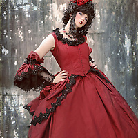 Fancy young woman looking regal with a large curly updo and historical red dress