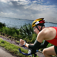 Nederland.Almere Haven.27 augustus 2005.<br /> Een van de tri-atleten fietsend langs het IJsselmeer tijdens de 40 km wielrennen, het 2e onderdeel van de Holland Triathlon. Sport.Wielrennen.Doorzettingsvermogen.Wielerhelm.Hollandse luchten.Water.Dynamiek.Sportief.Atletiek.<br /> Participants in the Holland Triathlon 2005.
