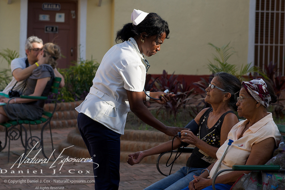 A nurse makes her rounds in the local plaza, helping elderly Cuban residents with their health needs. A couple kissing on the bench in the background. Trinidad, Cuba.