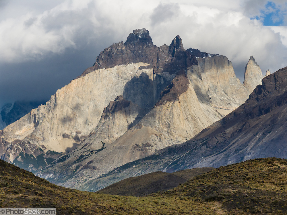 "Los Cuernos soar above Torres del Paine National Park, Chile, South America. ""The Horns"" (about 2100 meters elevation) are a pinkish-white granodiorite intrusion formed 12 million years ago topped with an older crumbly dark sedimentary rock, exposed by freeze-thaw erosion and glaciation. The foot of South America is known as Patagonia, a name derived from coastal giants, Patagão or Patagoni, who were reported by Magellan's 1520s voyage circumnavigating the world and were actually Tehuelche native people who averaged 25 cm (or 10 inches) taller than the Spaniards."